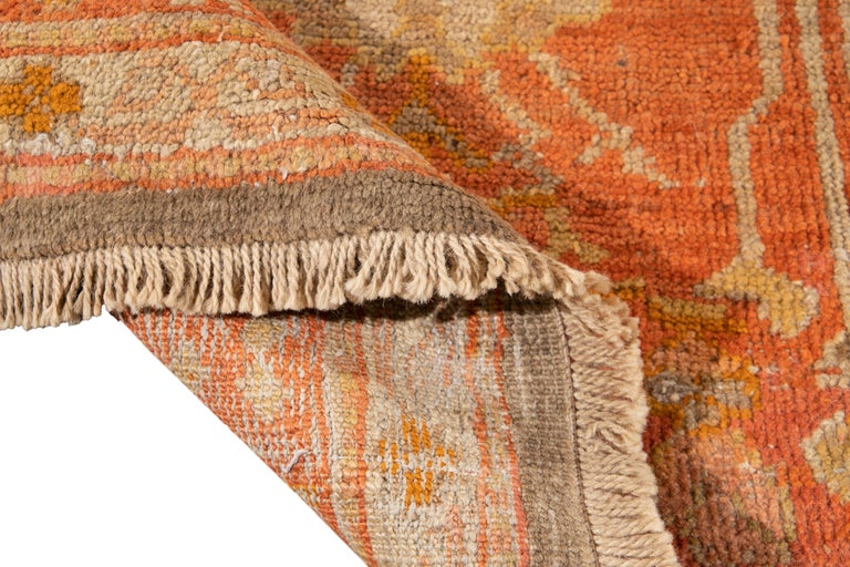 Beautiful Oversize Antique Oushak hand-knotted wool rug with an orange field, and multi-color accents in all-over geometric floral design.  This rug measures: 13' x 17'5