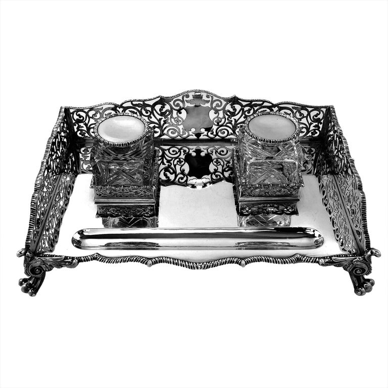 A magnificent antique Victorian solid silver ink stand with two heavy glass Inkwells with silver lids. The Inkstand has a rectangular form and stands on four impressive scroll feet. The sides of the inkwell have ornate pierced designs and a blank