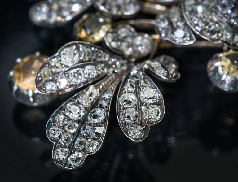 Circa 1840s  A large antique early Victorian era brooch is superbly modeled as a stylized flower. The brooch is finely crafted in silver-topped gold and embellished with champagne color topazes and sparkling bright white old mine cut