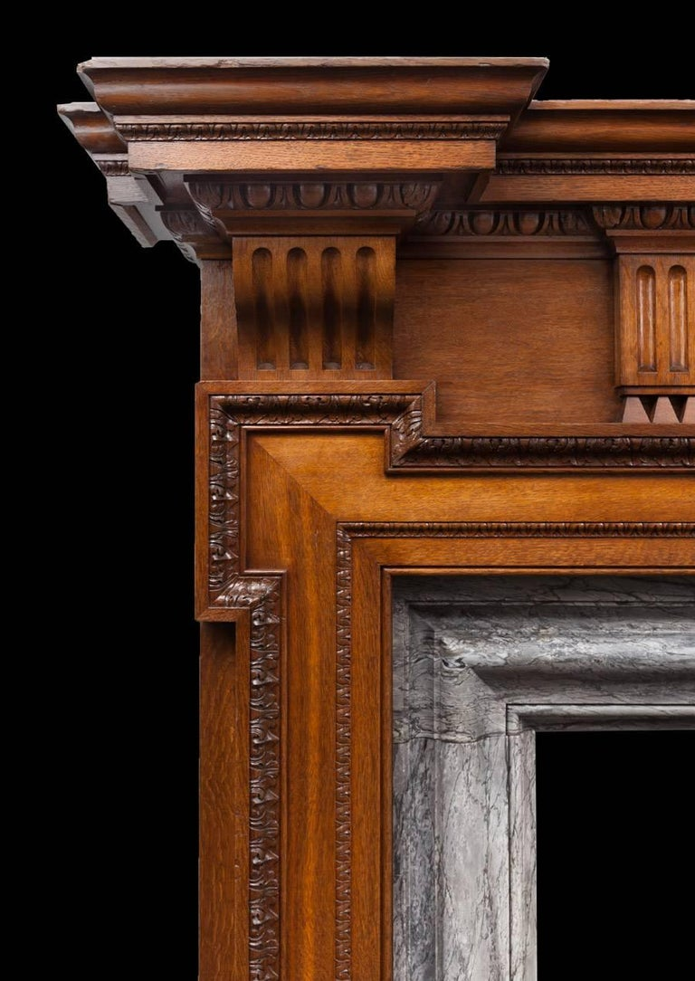 A very large antique carved oak and grey Bardiglio marble mantelpiece.