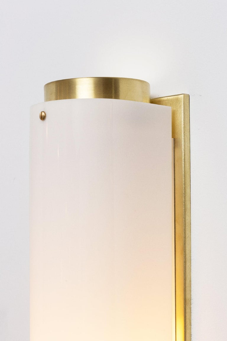 The arc sconce is made of a solid unfinished brass or black body and backplate with a white Lucite shade and brass screws.   Measures: Large: W 5.25in (13.5cm) x D 5.25in (13.5cm) x H 24.5in (62cm) Small: W 5.25in (13.5cm) x D 5.25in (13.5cm) x H