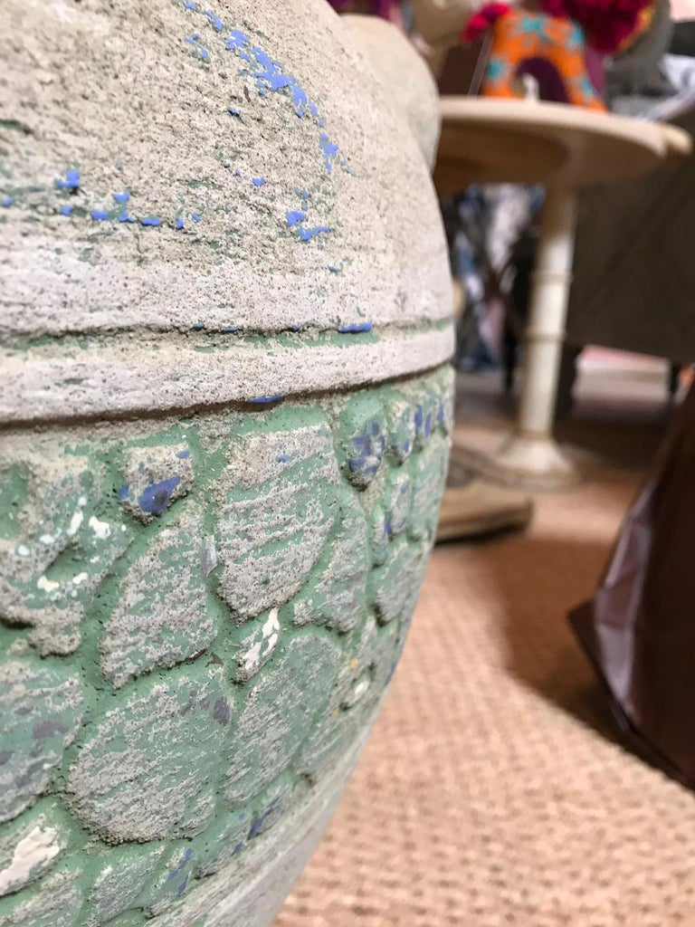 This pot is made from a hard porous, rock-like material. It has a section wrapped around it with decoratively pieced-together flower engravings. The section is a light leafy green strewn with spots of sky blue throughout the piece. The inside is