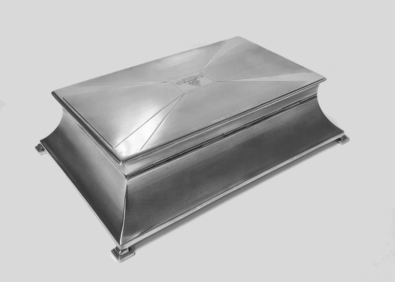 Large Art Deco silver box, Birmingham 1930 William Hutton & Sons. The unusual shape striking box on four bracket supports, the inverted tapered sides and cover with engine turned and polished silver ray design centering a cartouche engraved with the