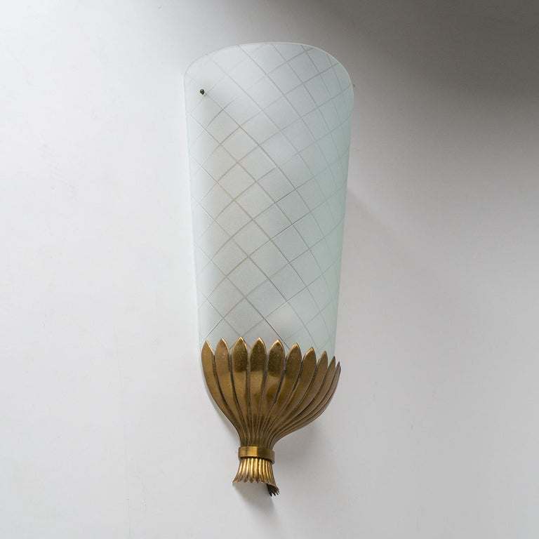 Rare oversized Art Deco wall light, from the 1930s. A large curved and satinated glass diffuser with geometric incisions sits on top of a lovely stylized brass bouquet. Very nice original condition with some patina on the brass. Two original brass