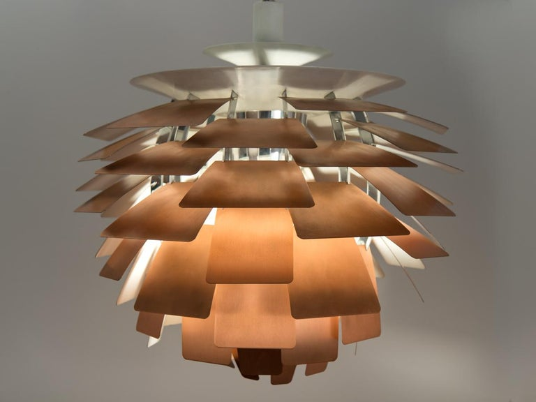 Monumental pendant lamp by Poul Henningsen for Louis Poulsen. Suspended by ivory enameled-steel canopy, the interior chrome cylinder is surrounded by layers of brushed copper leaves. Each brilliant leaf is configured so that the lamp emits a