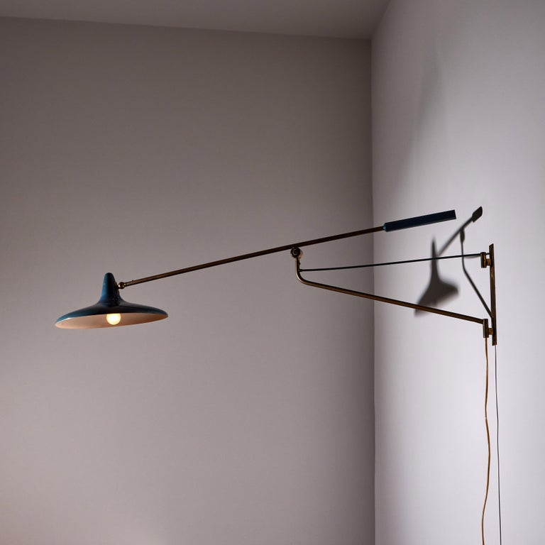Large articulating wall light by Stilnovo. Manufactured in Italy, circa 1950's. Original enameled metal, brass. Wired for U.S. standards. Arm and shade articulate to various positions. We recommend one E27 60w maximum bulb. Bulb provided as a one