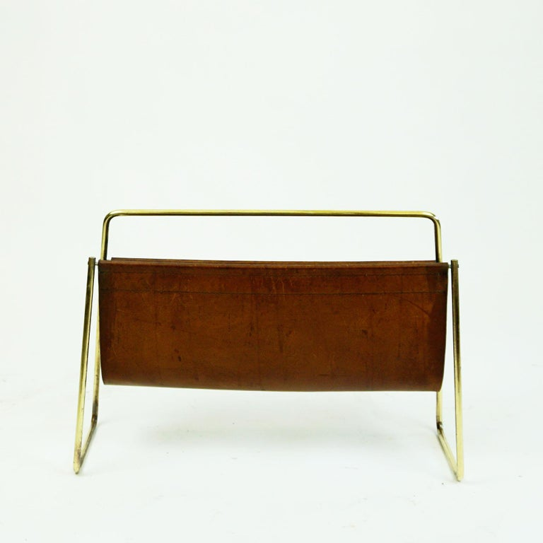 Iconic large Austrian mid-century newspaper or magazine rack designed by Carl Auböck II from early 1950s and manufactured by Auböck Werkstätte in Vienna. It's made of solid brass and brown leather and is in very good condition, without any losses