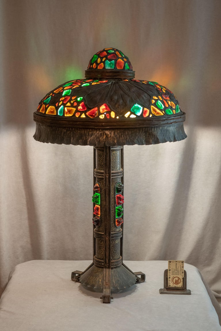 We have sold many Austrian table lamps with chunk jewel glass, but this may well be the best we have ever offered. Besides the extra large size, the design, the jeweled base, and the hammered metal work, it's most striking and colorful. The top of