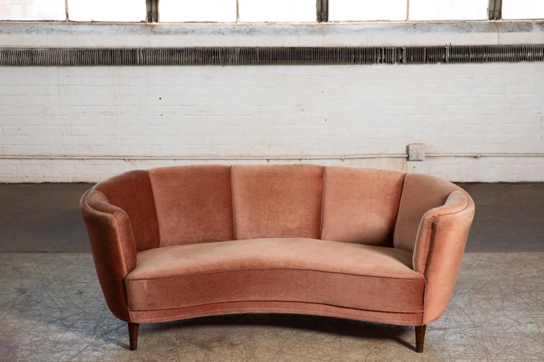 Beautiful and very elegant 1940-50s large size curved three-seat sofa in pink mohair fabric. The sofa has springs in the seat and the backrest and the cushions are nice and firm and the sofa solid and sturdy. The mohair wool fabric is showing wear