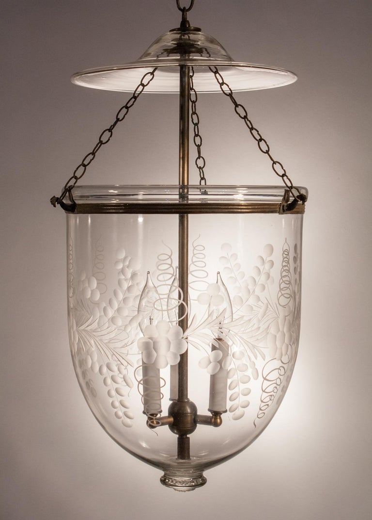 A superb quality hand blown glass bell jar lantern with wonderful form and an etched floral motif. This larger-sized pendant light features its original smoke bell, rolled brass band and suspension chains. It has been newly electrified with a