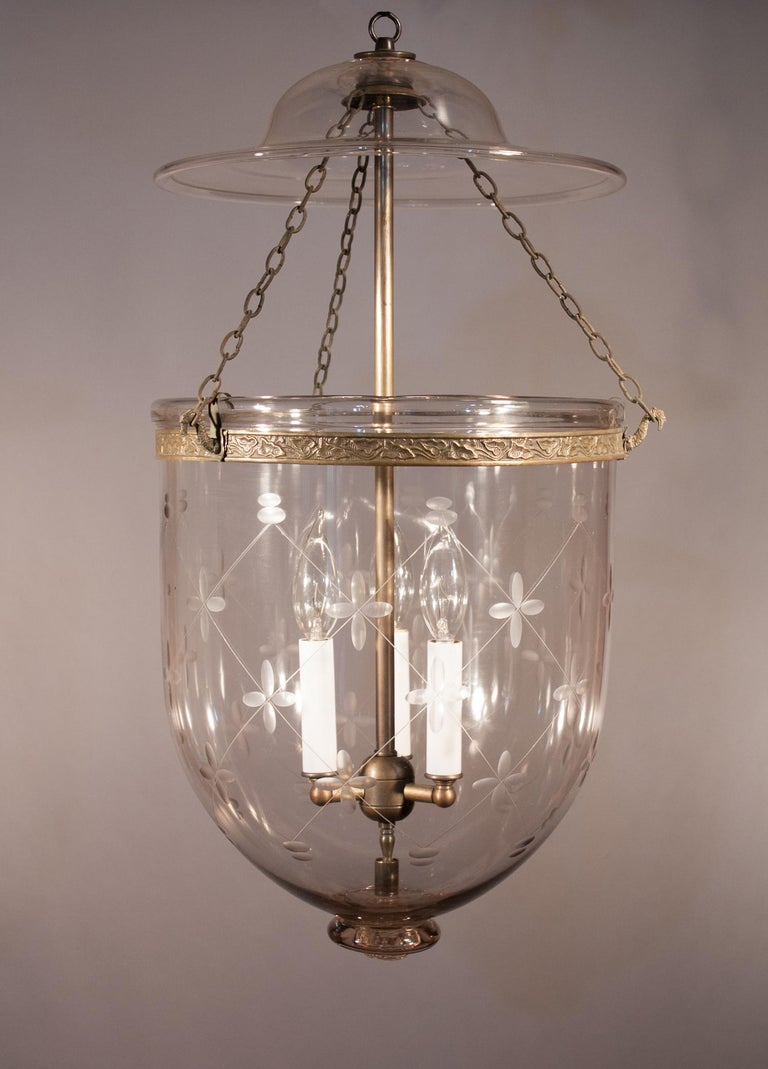 An exceptional antique English bell jar lantern with its original bell-shaped smoke lid and brass band with embossed vine design. The quality of this circa 1870 pendant is excellent, with a number of desirable air bubbles in the hand blown glass.