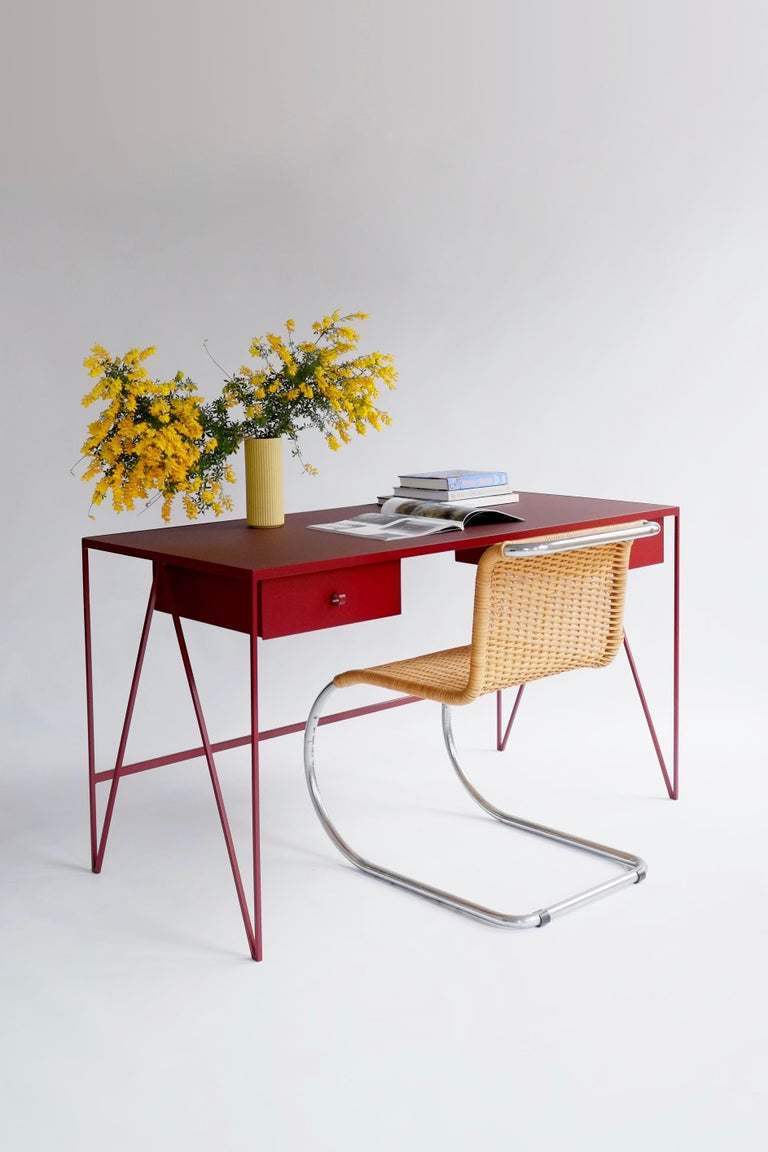 This large beetroot color study desk is made with a powder coated steel frame and a beautiful natural linoleum top made out of linseed oil. This modern minimal desk has two steel drawers suspended underneath the tabletop with our Loop handles. The