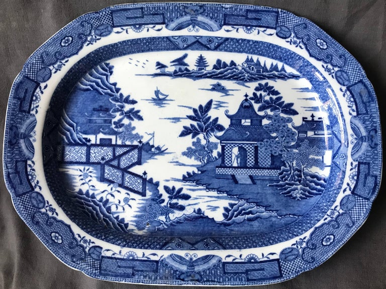 Large blue and white chinoiserie platter. Large Davenport platter with rich blue border of butterflies framing pagoda in a lagoon with fretwork fencing and figures. England, mid-19th century. Dimensions: 16.88