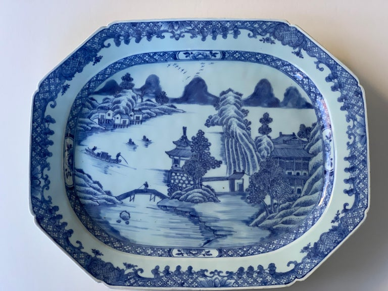 This large hand-painted blue and white Chinese porcelain platter was made in the 18th century, Qianlong period, circa 1780.  The scene shows a harbor with flower-filled trees, pagodas, rockwork, and distant mountains. Small details add to the