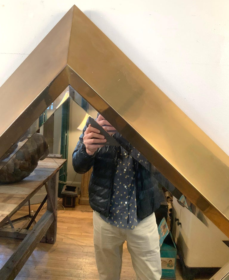 A large and stunning 1970s wall mirror with a deep and wide dramatic brass frame in diamond form, with a beveled mirror inset. Designed by Marcello Mioni. The brass has some finish loss and slight discolorations, but no dents or scratches. The scale