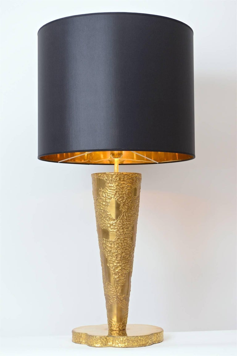 A wonderfully impressive sculptural brass table lamp in the manner of Angelo Brotto, Italy, circa 1970. Its large tapered stem sits on a thick freeform base and is complemented by a beautiful cotton shade with gold coloured inner lining. Completely