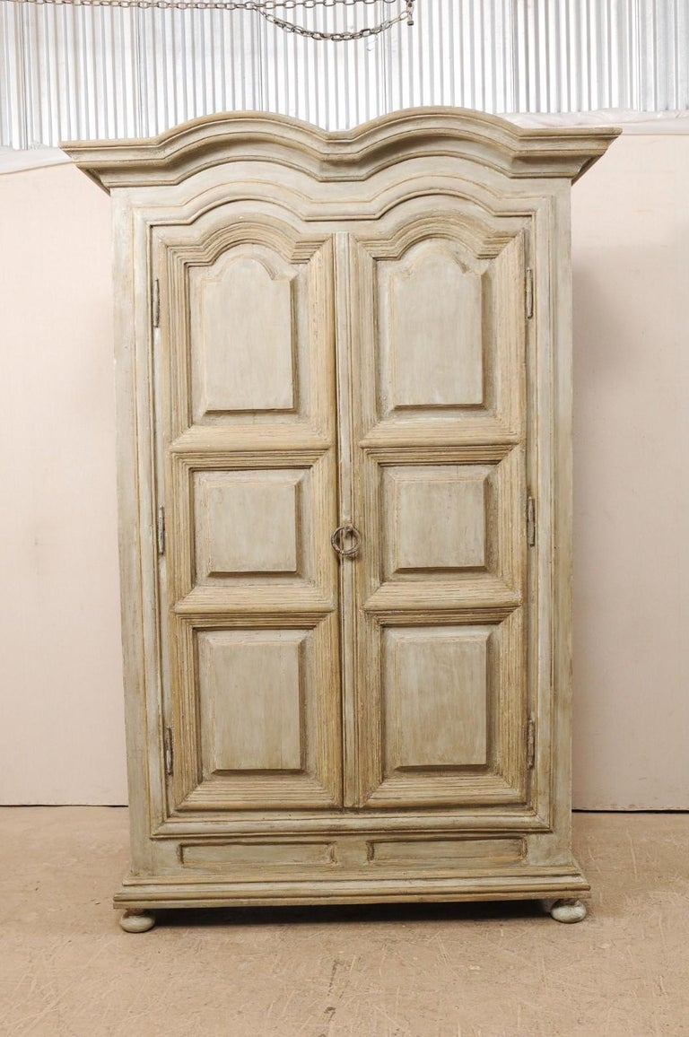 A large sized Brazilian painted wood storage cabinet from the mid-20th century. This vintage cabinet from Brazil features a thickly molded, double hooded pediment, atop two decoratively carved raised panel doors, and is presented upon bun style