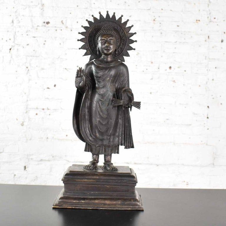 Handsome large patinated bronze Tibetan standing Buddha sculpture with a beautiful halo. It is in wonderful vintage condition. Please see photos, circa 20th century.  We were presented this beautiful example of Buddha and knew it would be one we