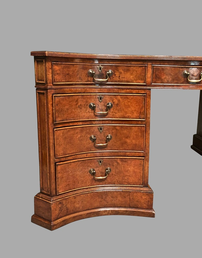 An impressive English Georgian style burl elm serpentine form partners desk of large-scale, the brown gilt-tooled leather top with a molded edge above three frieze drawers, each pedestal with three additional drawers, the reverse with cupboard