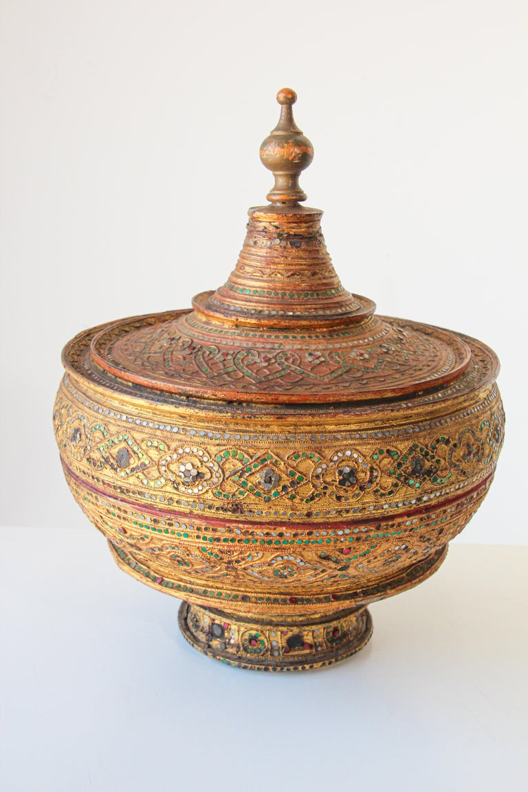 A very large Asian Burmese gilt and lacquered wood bamboo offering vessel, container adorned with mirror and jewels colored gems with a conical removable top. Burmese temple offering covered box, with a red lacquer interior, richly decorated with