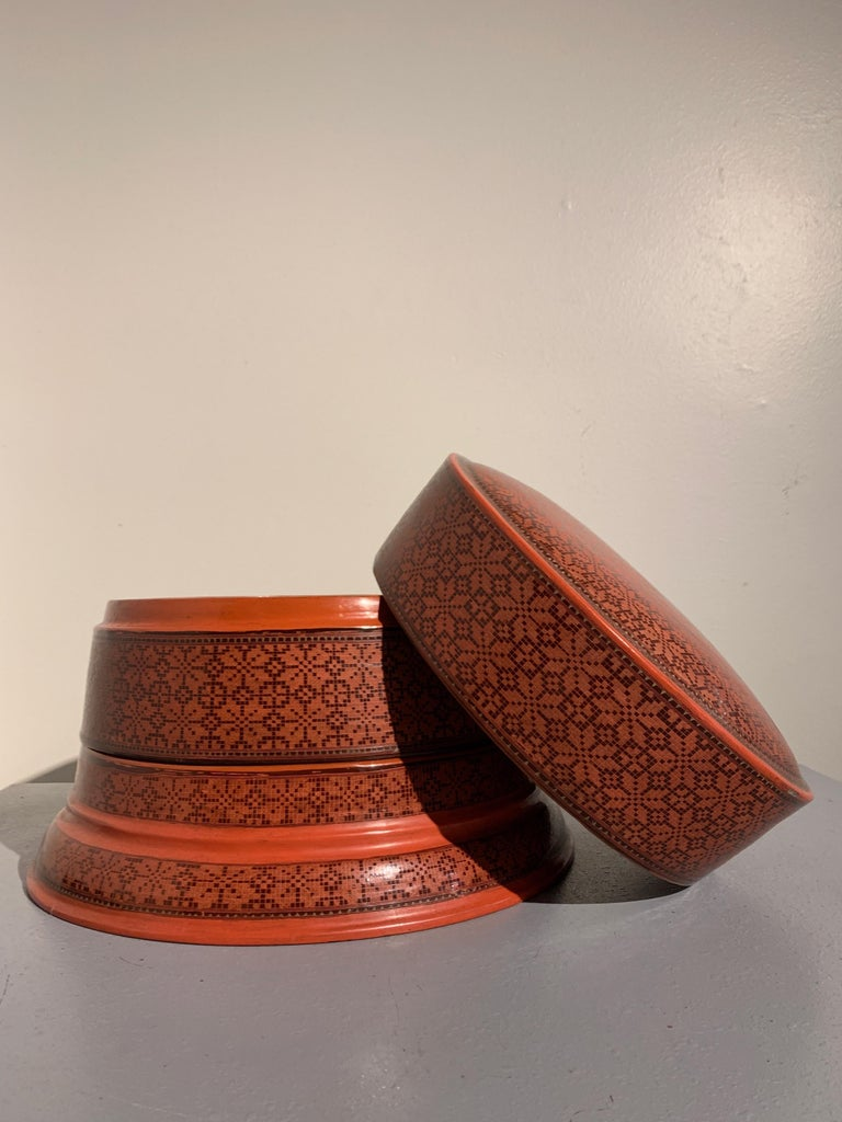A striking and finely decorated Burmese red lacquer two-tiered round storage box and cover, called a bi-it, Bagan, Burma (Myanmar), early to mid-20th century.  The round box comprised of three parts, two compartments and a lid - originally used to
