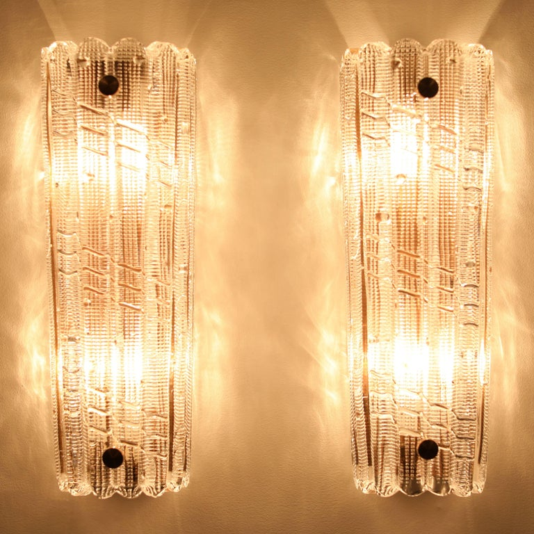 Large and stunning pair of thick mold-blown-glass sconces by Carl Fagerlund for Orrefors, Sweden, circa 1970s. The glass has cross-hatching and ribbing, producing a beautiful glow when lit. Each piece of glass tapers slightly from 5.25
