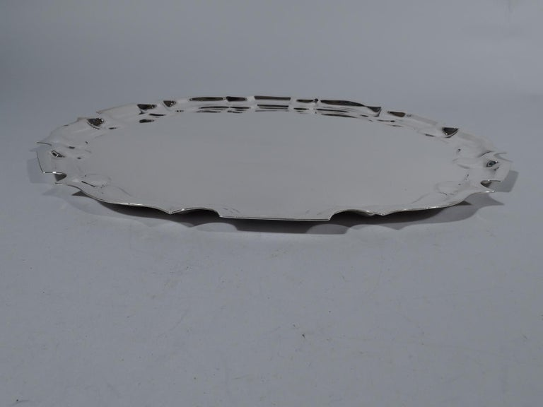 Traditional sterling silver serving tray, circa 1950. Retailed by Cartier in New York. Round with flat curvilinear Georgian piecrust rim. Fully marked including maker's (Graff, Washbourne & Dunn) and retailer's stamps and no. 64. Weight: 31 troy