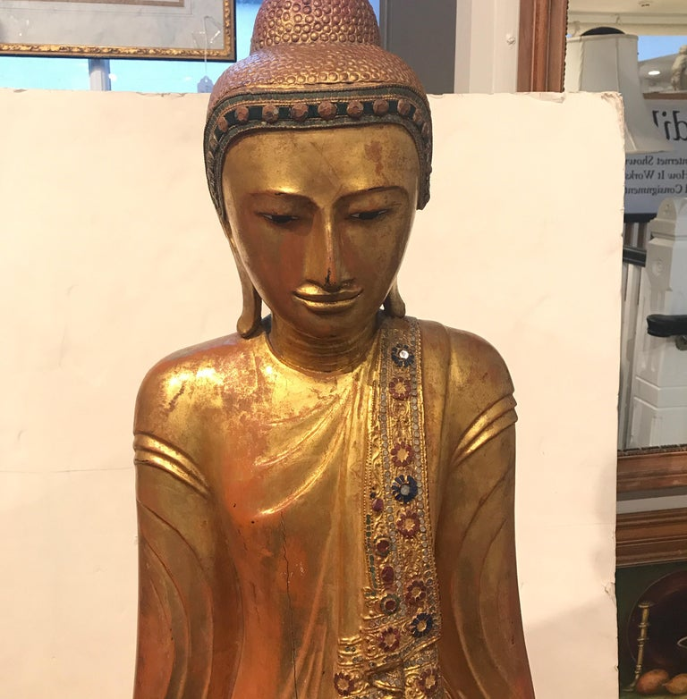 A solid carved wood Thai sculpture of Buddha. The original gold surface with slight wear, decorated with tiny colored mirror trim all around the surface of the clothing. The total height is 61 inches, the total height of just the sculpture is 55