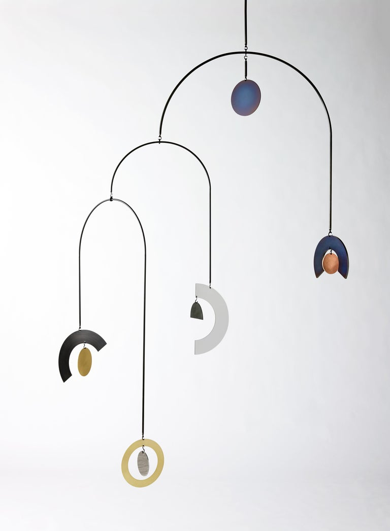 An undulating composition of discs, rings, half moons and rainbows cascade from large sweeping arcs to create a hypnotic hanging sculpture. Each object has a unique patina that draws inspiration from our solar system. Surface textures that recall