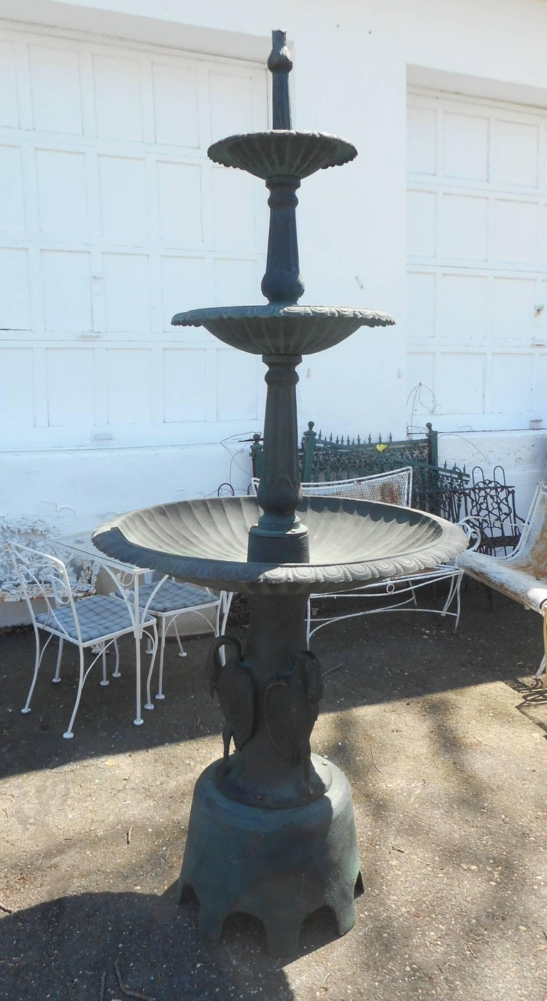This impressive cast iron fountain features three reservoirs and an unusual base with egrets. The water gracefully flows from the top into each reservoir. A sturdy circular base with several egrets around it adding to the feeling of serenity.