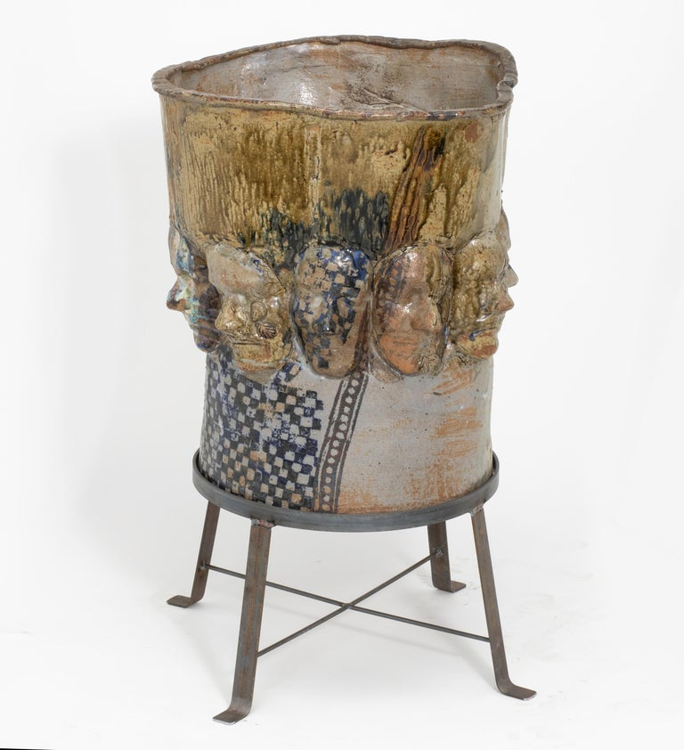 """Very unusual, artisan handmade, ceramic planter pot on iron base stand. Very sculptural with panorama of faces in relief around the pot. Glazed in various blue and green earth tones. A unique art piece. Pot size. Only. 19"""" diameter x 21"""" high."""