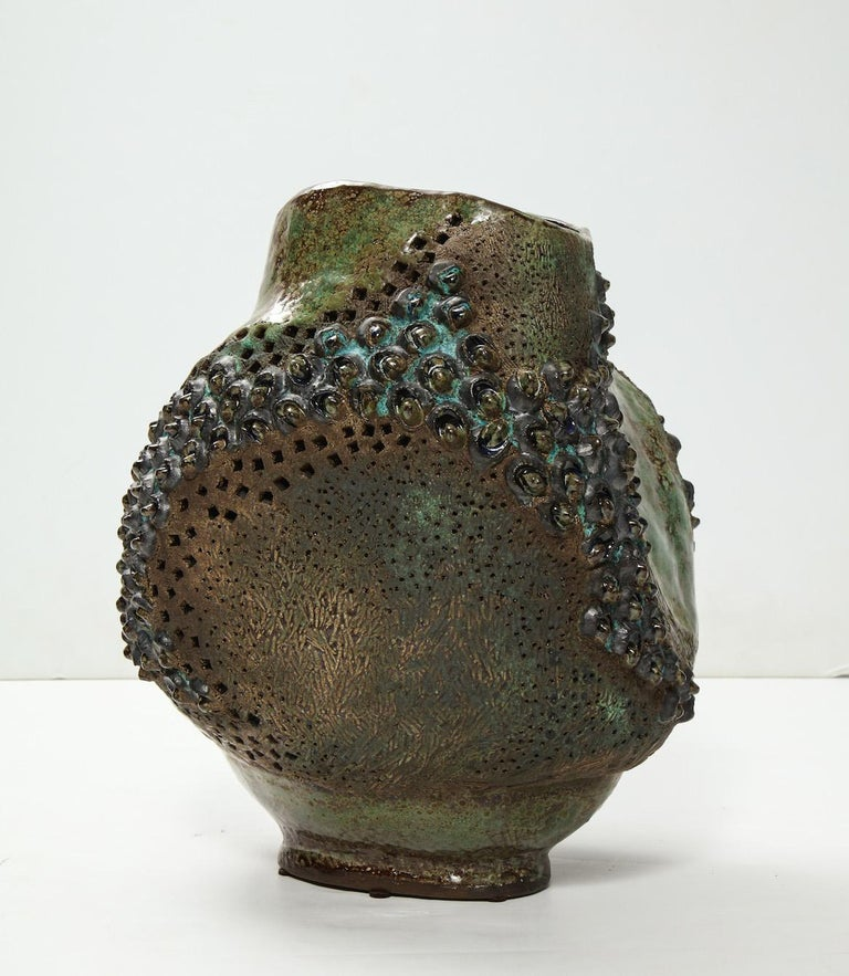 Fantastic hand-built vessel with great texture, irregular form and patterned holes throughout. High-fired glazes in earth tones. Artist signed and dated on underside.