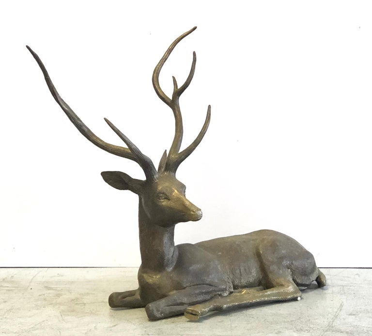 A large brass sculpture of a reclining deer. Striking pose and fine detail in the rendering.