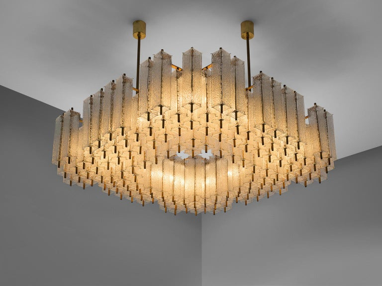 Chandelier, in glass and brass, Europe, 1970s.   Large square chandelier with a great amount of rectangular structured glass shades. The frame is made of brass and holds numerous structured glass 'tubes' with a brass center. Due the combination of