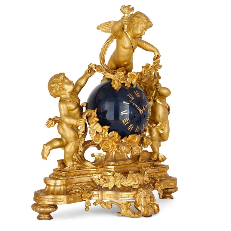 Large cherub-themed gilt bronze clock garniture by Popon French, late 19th Century Clock: Height 68cm, width 63cm, depth 26cm Candelabra: Height 89cm, width 46cm, depth 39cm  This beautiful three-piece clock set is crafted from gilt bronze in