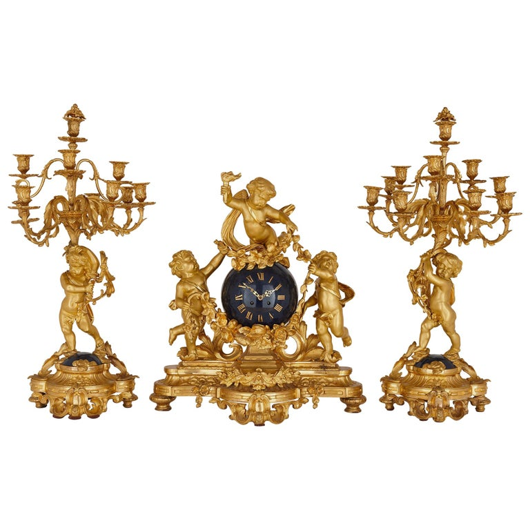 Large cherub-themed gilt bronze clock garniture by Popon For Sale