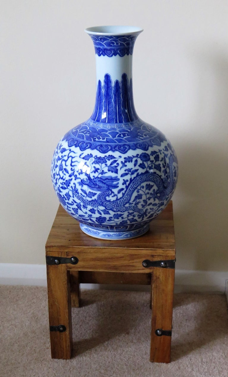 This is a very elegant and beautifully hand painted porcelain Chinese bottle vase raised on a footed base and dating to the Late Qing period, circa 1900.  This vase has a classic bottle shape raised on a low foot and with a slightly flaired rim.