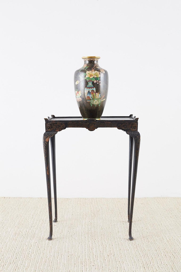 Dramatic large Chinese cloisonné vase featuring a flower vase decoration on one side and a gourd on the back. The decoration stands out against a black ground with cloud patterns covering the entire vase. The baluster form body has a gilt bronze lip