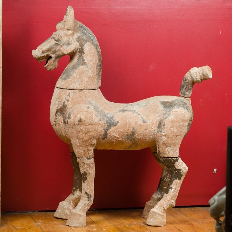 A large Chinese Han dynasty period terracotta horse sculpture circa 202 BC-200 AD, with mineral deposits. Handmade in China during the prestigious Han dynasty and made in several parts (the head, tail and legs come off), this large Chinese