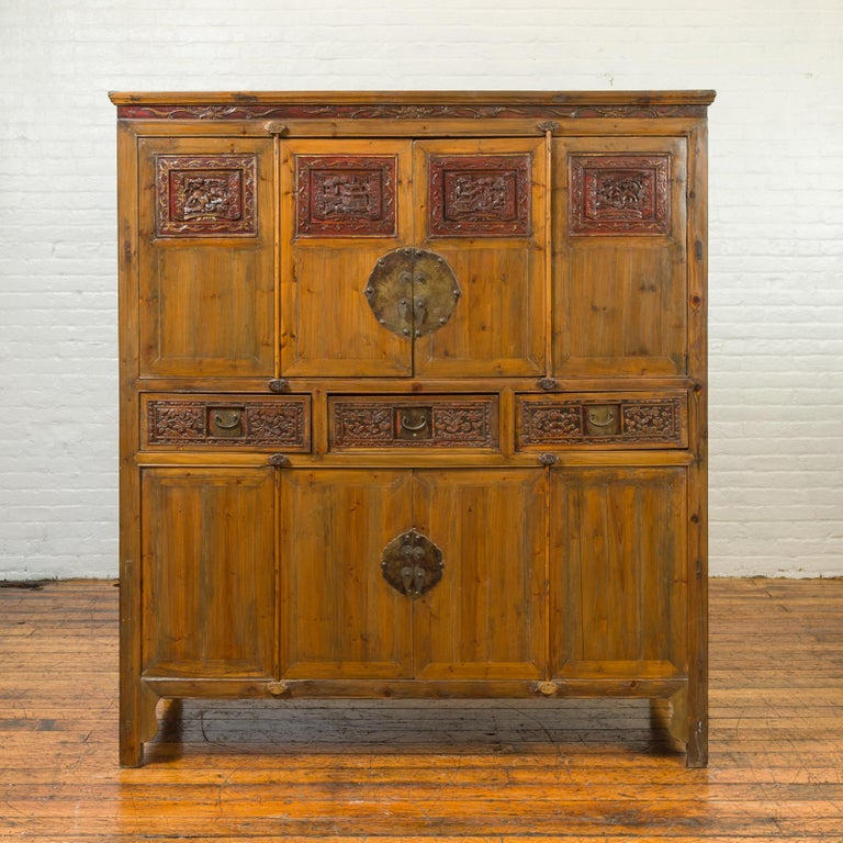 A large Chinese Qing Dynasty elmwood armoire from the 19th century, with hand carved panels, red lacquered accents and bronze hardware. Created in China during the 19th century, this elm armoire features a thin cornice resting upon a perfectly