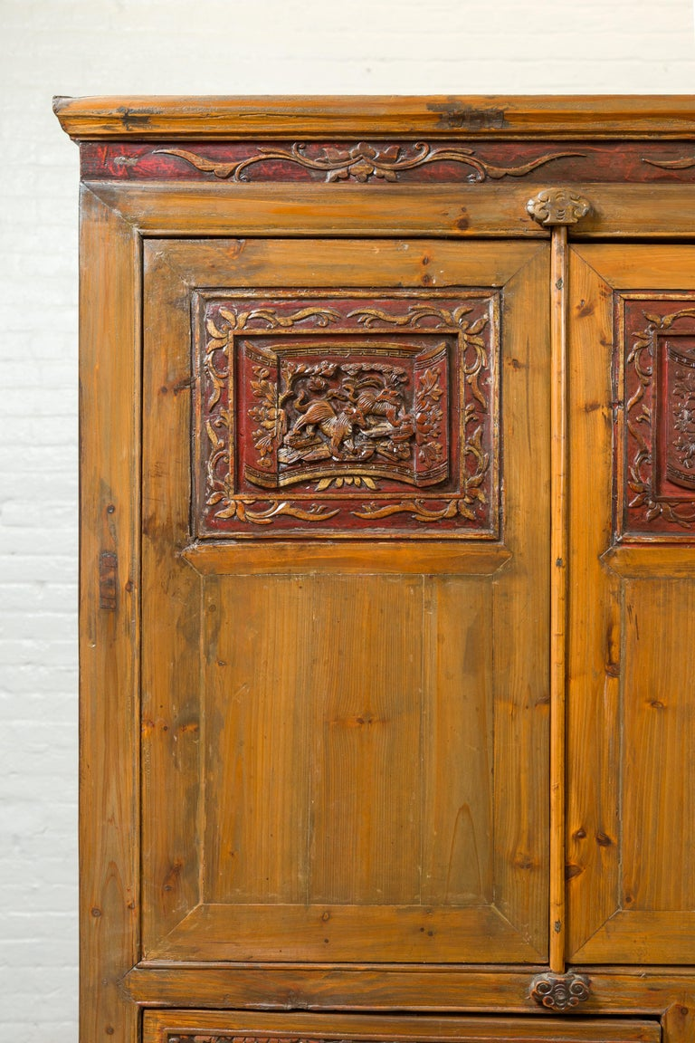 Large Chinese Qing Elm Armoire with Carved Motifs and Red Lacquered Accents In Good Condition For Sale In Yonkers, NY