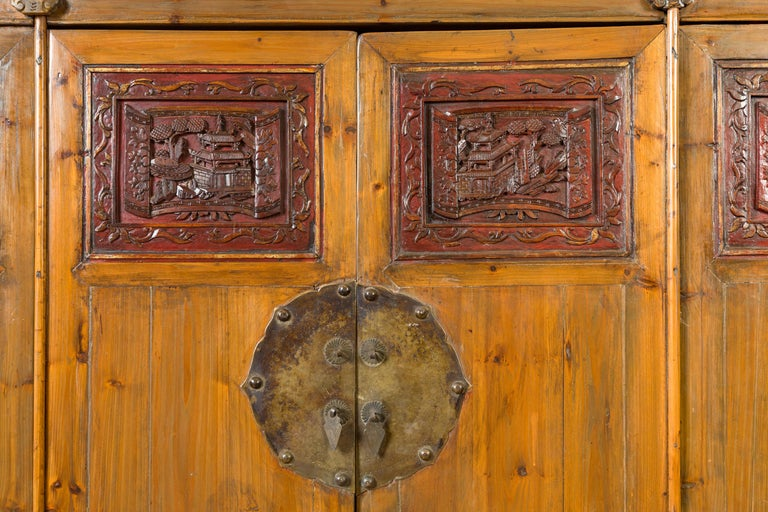 19th Century Large Chinese Qing Elm Armoire with Carved Motifs and Red Lacquered Accents For Sale