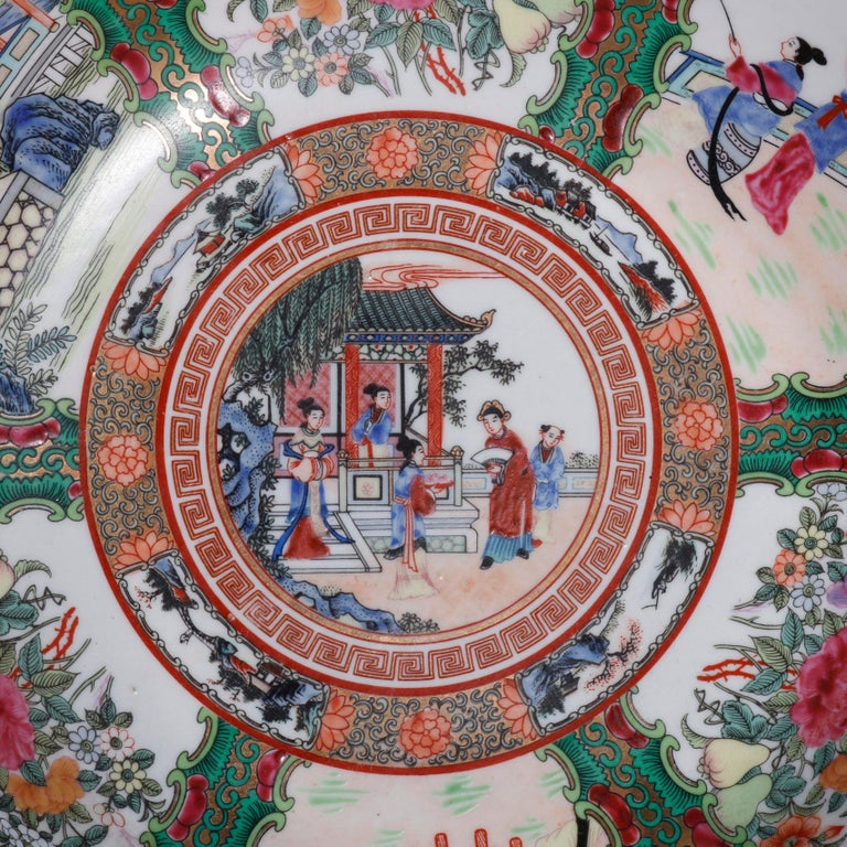 A large Chinese Rose Medallion porcelain center bowl offers hand painted enameled genre and garden reserves including figures, birds, animals, flowers, and pagoda structures, bordered with foliate elements and Greek key banding, gilt highlights
