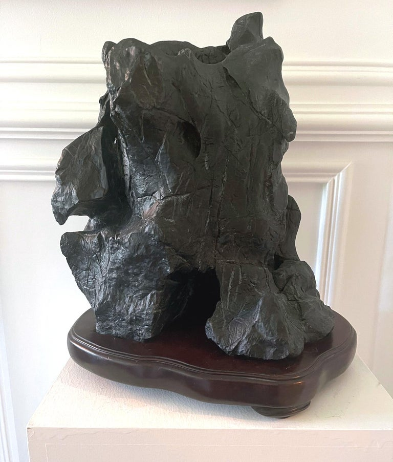 An impressive Chinese scholar stones (also known as Gong Shi, meditation stone and spirit rock) on display wood stand circa late 19th century to early 20th century. This mountain-form Lingbi stone features a nearly complete black surface with very