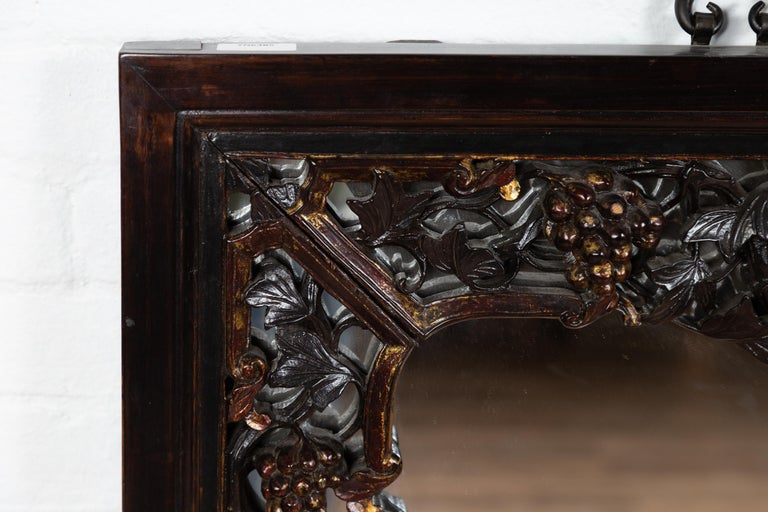 A large Chinese vintage hand carved mirror from the mid-20th century, with flowers and fruits of the earth. Born in China during the midcentury period, this elegant wall mirror charms our eyes with its dark patina accented with discreet gilt