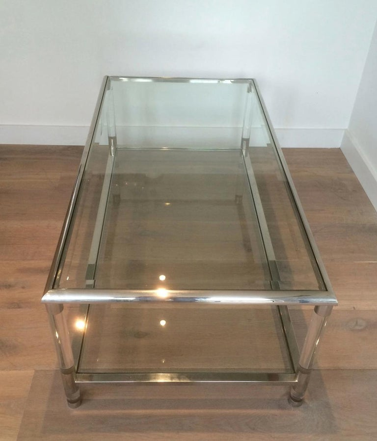 This large coffee table is made of chrome and Lucite with two glass shelves, beveled on top glass. This is a French design, circa 1970.