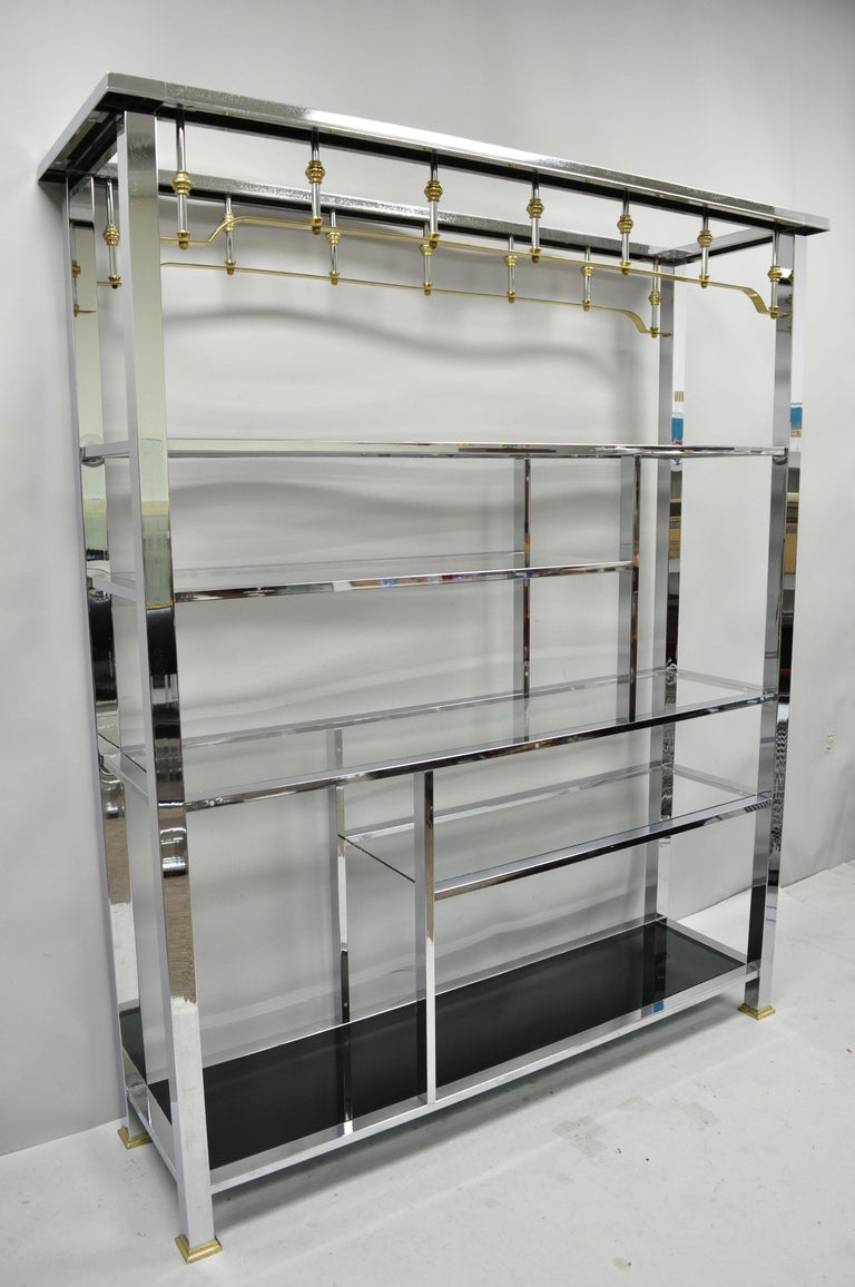 Large vintage chrome and brass Hollywood Regency Mid-Century Modern étagère display shelf. Item features a large impressive size, various shelf length and height, brass accents, 5 glass shelves, smoked glass lower shelf, very nice vintage item,