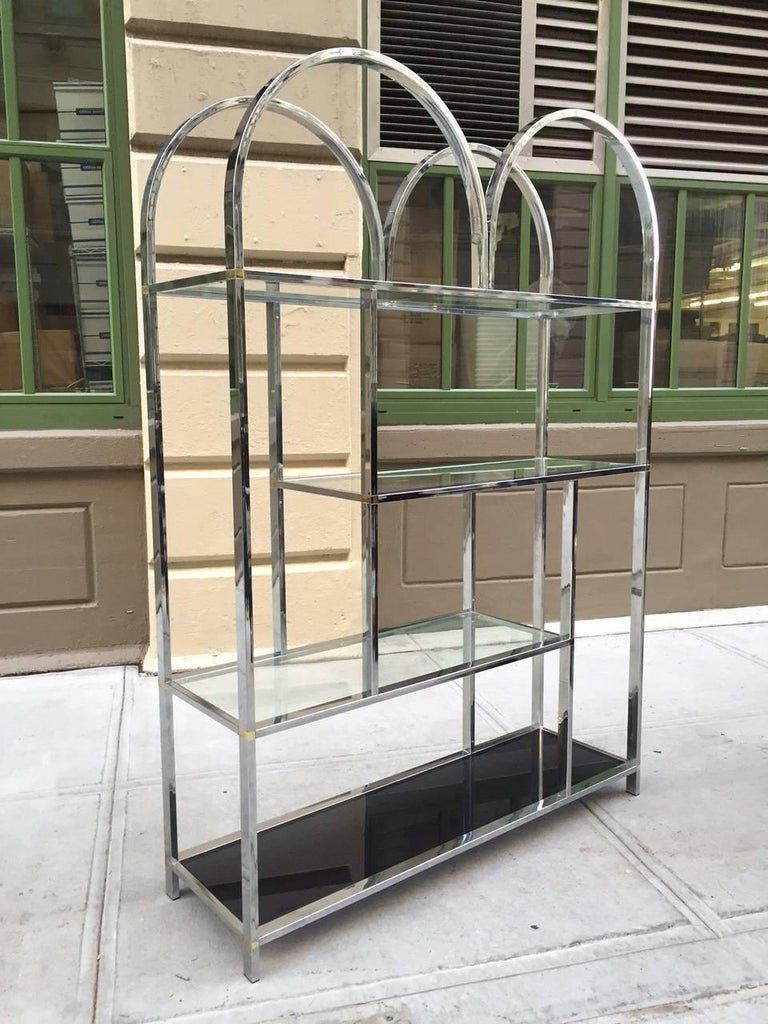 Large chrome étagère style of Milo Baughman. Has curved top, four glass shelves (smoked glass to the bottom), and brass accents.