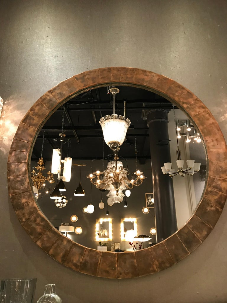 Oversized circular mirror surrounded by a naturally patinated copper frame.