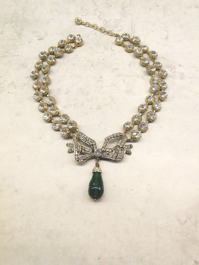 This stunning, classic necklace is made from clear pastes, in gilt metal settings, with a large paste bow as the centrepiece, from which hangs a large emerald poured glass drop. It is a perfect example of the long collaboration between Chanel and